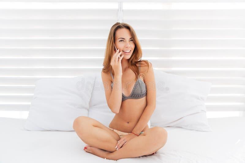 Aantrekkelijk glimlachend meisje in bikini die op de telefoon spreken stock afbeeldingen