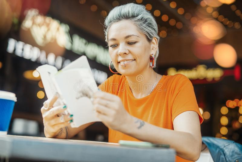 Aantrekkelijk het glimlachen de lezingsboek van het blondemeisje bij koffie en opzij het kijken stock afbeelding