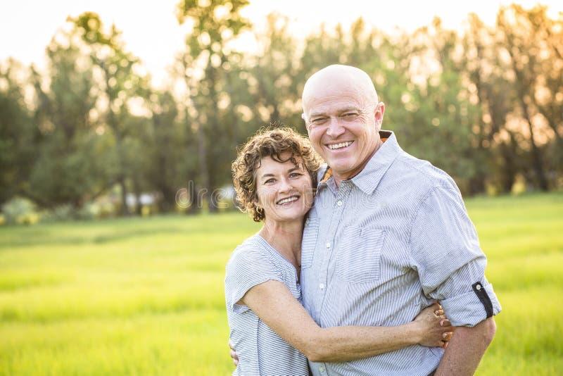Aantrekkelijk het Glimlachen Rijp paarportret in openlucht stock foto's