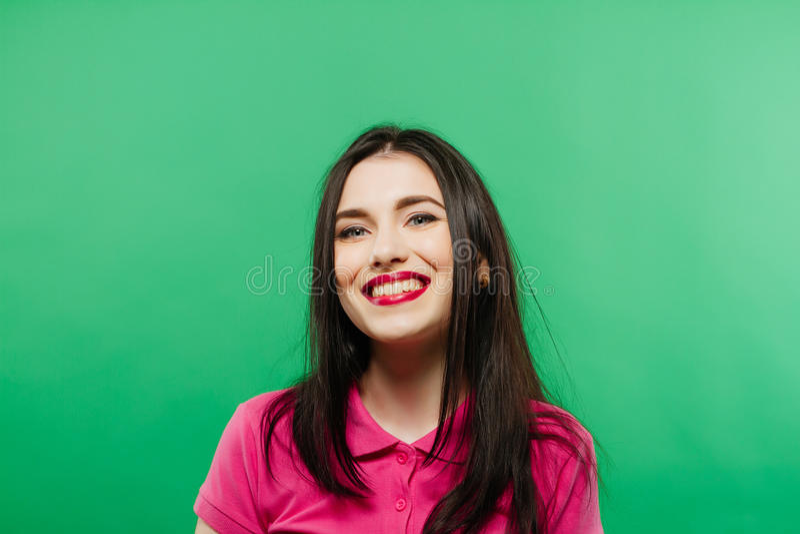 Aantrekkelijk het glimlachen vrouwenportret op groene achtergrond stock foto