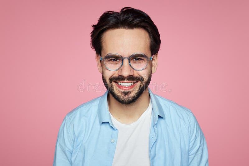 Aantrekkelijk hipstermannetje die bij camera, blij om geschikte goed betaalde die baan te vinden glimlachen, over roze achtergron royalty-vrije stock afbeelding
