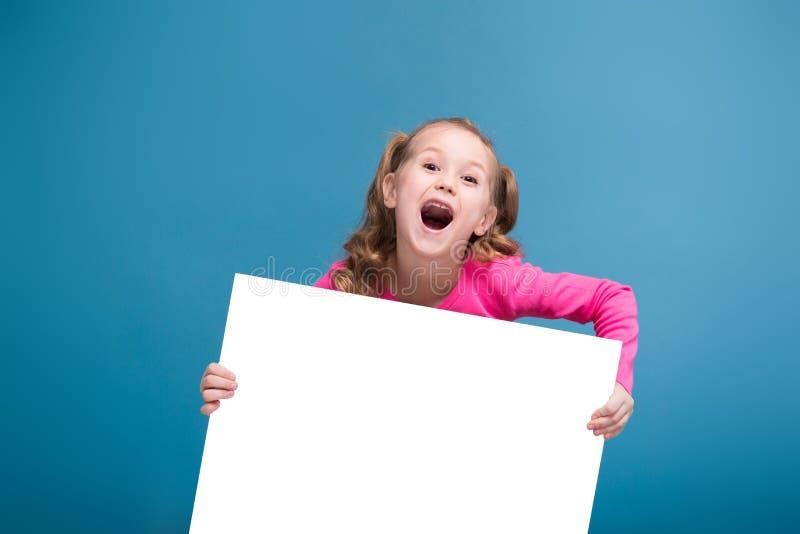 Aantrekkelijk houden weinig leuk meisje in roze overhemd met aap en blauwe broeken lege affiche stock afbeeldingen