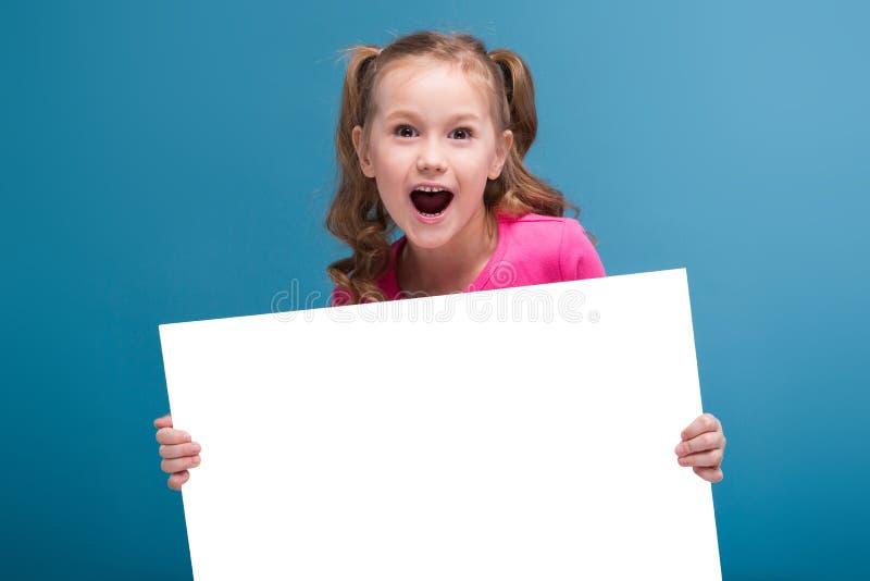 Aantrekkelijk houden weinig leuk meisje in roze overhemd met aap en blauwe broeken lege affiche stock foto