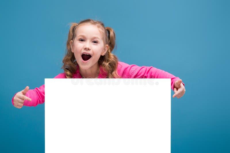 Aantrekkelijk houden weinig leuk meisje in roze overhemd met aap en blauwe broeken lege affiche royalty-vrije stock afbeelding