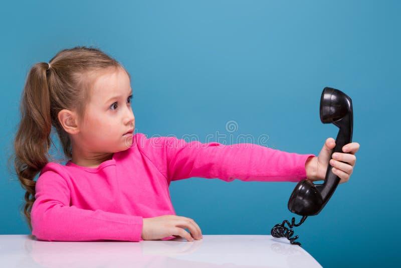 Aantrekkelijk houden weinig leuk meisje in roze overhemd met aap en blauwe broeken lege affiche en besprekingen een telefoon royalty-vrije stock afbeeldingen