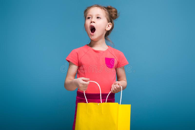 Aantrekkelijk houdt weinig leuk meisje in roze kleding gele document zak royalty-vrije stock afbeelding