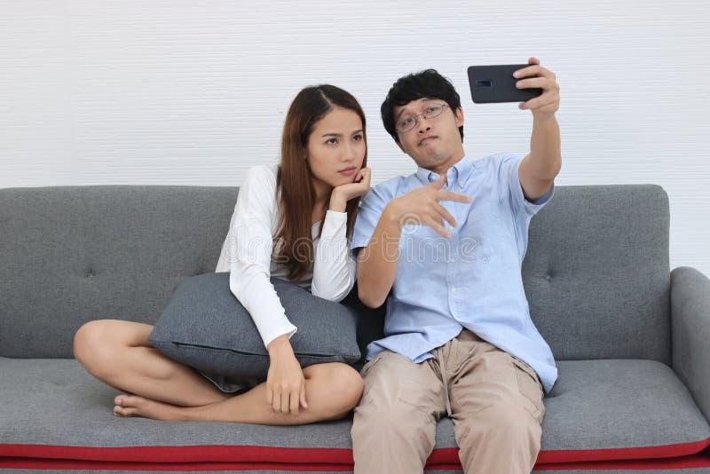 Aantrekkelijk jong Aziatisch paar die een foto of selfie samen in woonkamer nemen Liefde en Romaans mensenconcept stock foto