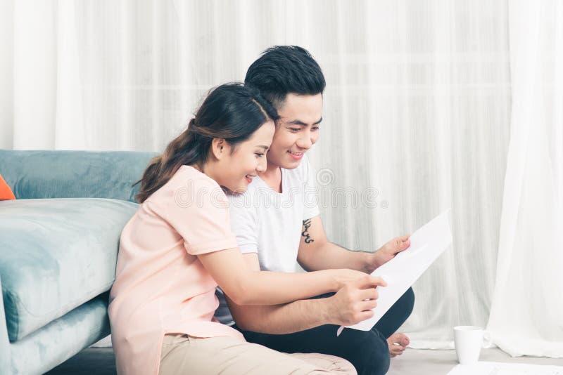 Aantrekkelijk jong Aziatisch volwassen paar die huisplannen bekijken stock foto's