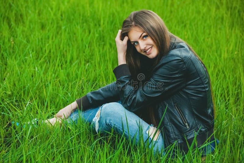 Aantrekkelijk, jong blondemeisje in een grijze laag en jeans die op gras en glimlach zitten stock fotografie