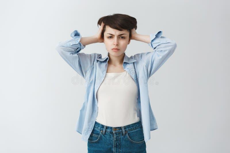 Aantrekkelijk jong donker haired studentenmeisje die in vrijetijdskleding handen op hoofd houden, na examensweek worden vermoeid royalty-vrije stock afbeelding