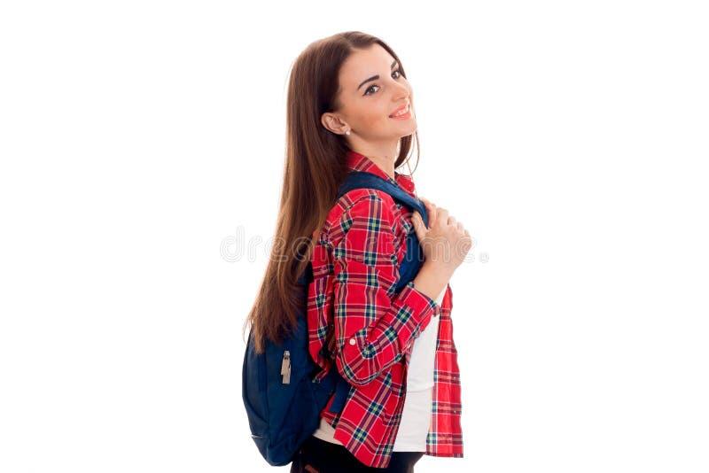 Aantrekkelijk jong donkerbruin studentenmeisje met blauwe rugzak dat op witte achtergrond wordt geïsoleerd stock fotografie