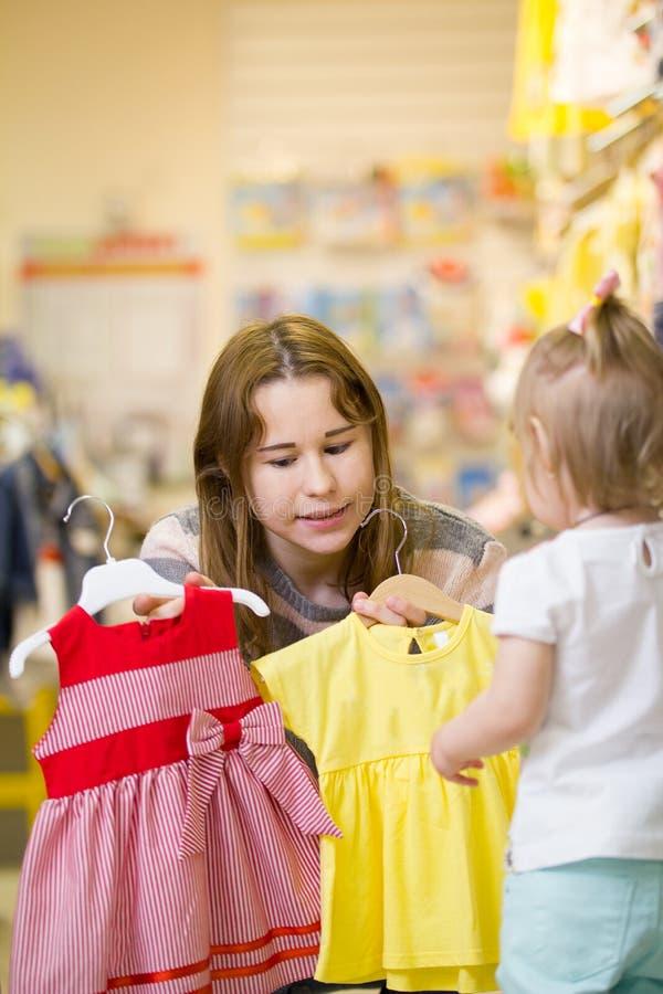 Download Aantrekkelijk Jong Mamma Die Kleding Met Haar Dochter Kiezen Stock Afbeelding - Afbeelding bestaande uit markt, kleding: 114225953