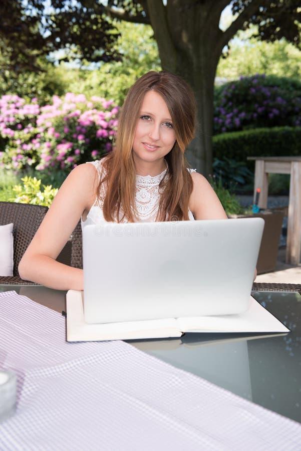 Aantrekkelijk jong meisje die in de tuin aan laptop werken stock foto's