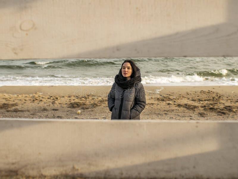 Aantrekkelijk jong meisje die zich op het zand tegen de achtergrond van het overzees bevinden mening door een houten omheining ge stock afbeeldingen
