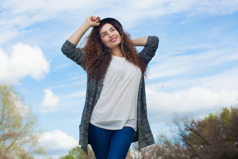 Aantrekkelijk, jong meisje in jeans en een zwarte hoed, die op de achtergrond van hemel glimlachen royalty-vrije stock afbeeldingen