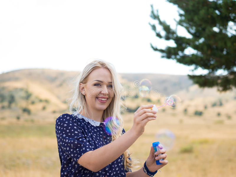Aantrekkelijk jong meisje met zeepbels in aard royalty-vrije stock afbeelding