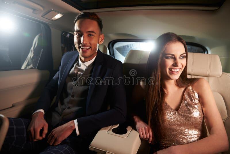Aantrekkelijk jong paar die in de rug van een limousine lachen stock foto's