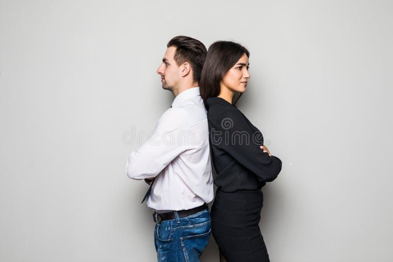 Aantrekkelijk jong paar die zich rijtjes allebei die zorgvuldig in de afstand met stille glimlachen, op grijs staren bevinden royalty-vrije stock fotografie