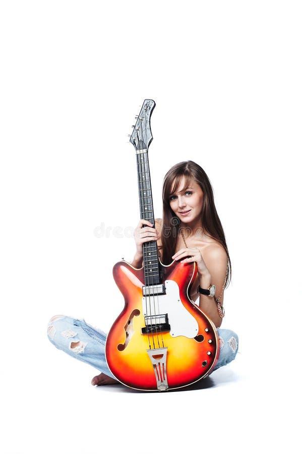 Aantrekkelijk jong wijfje dat een gitaar houdt stock afbeeldingen