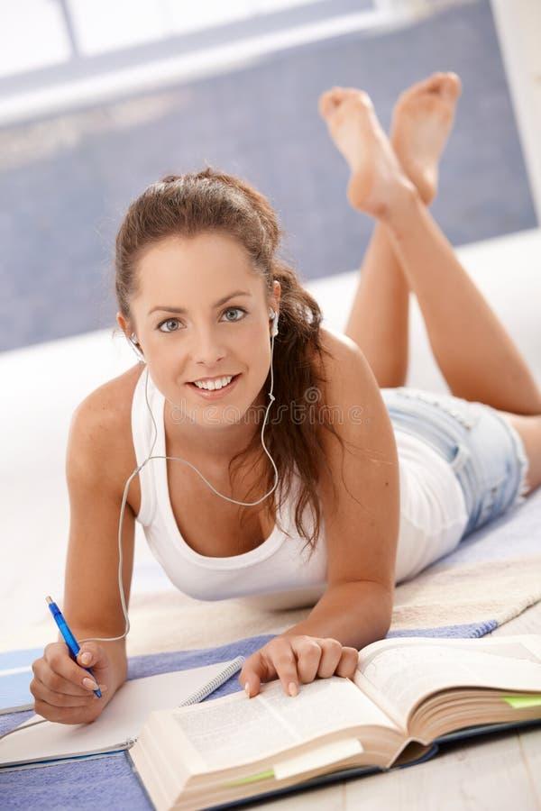 Aantrekkelijk jong wijfje dat thuis op vloer bestudeert stock foto's