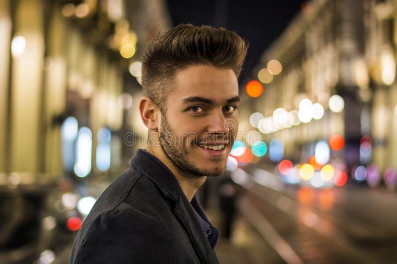 Aantrekkelijk jonge mensenportret bij nacht met stadslichten stock afbeelding