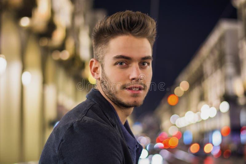Aantrekkelijk jonge mensenportret bij nacht met stadslichten stock fotografie