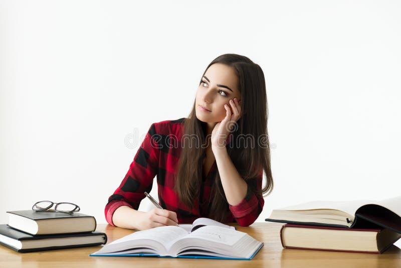 Aantrekkelijk Kaukasisch meisje die voor haar examens thuis bestuderen, onderwijsconcept royalty-vrije stock foto's
