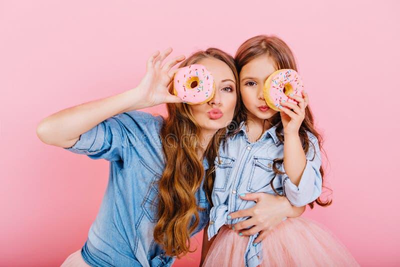 Aantrekkelijk krullend meisje in denim shirt dat kleine zusjes omarmt en grappig poseren met heerlijke donut op roze achtergrond stock foto