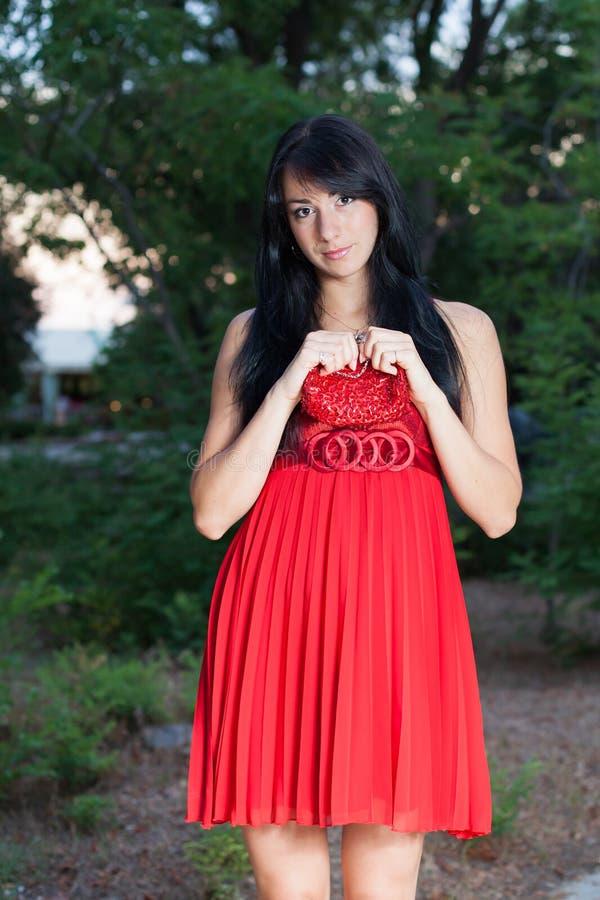 Aantrekkelijk langharig brunette in rode sundress die in park stellen royalty-vrije stock fotografie