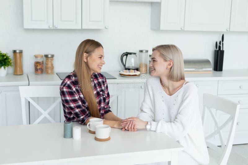 Aantrekkelijk lesbisch wijfje twee die in vrijetijdskleding samen bij de lijst in de keuken zitten, die elkaar bekijken stock foto's