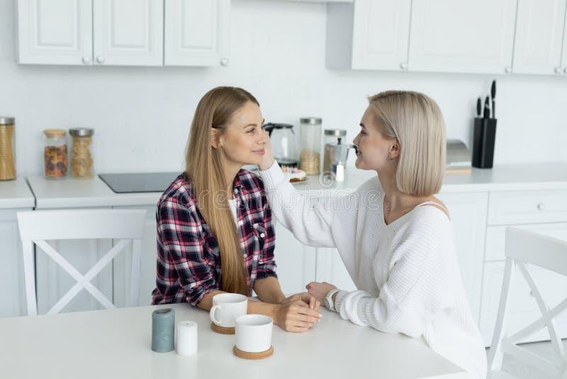 Aantrekkelijk lesbisch wijfje twee die in vrijetijdskleding samen bij de lijst in de keuken zitten, die elkaar bekijken royalty-vrije stock foto