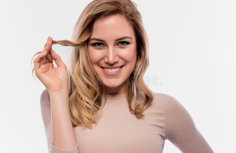 Aantrekkelijk leuk blonde Close-upportret op een wit Mooie jonge vrouw in een vlees-gekleurde kleding royalty-vrije stock afbeeldingen