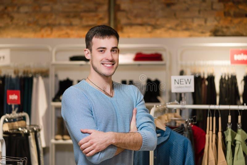 Aantrekkelijk mannelijk verkopersportret bij klerenopslag stock foto