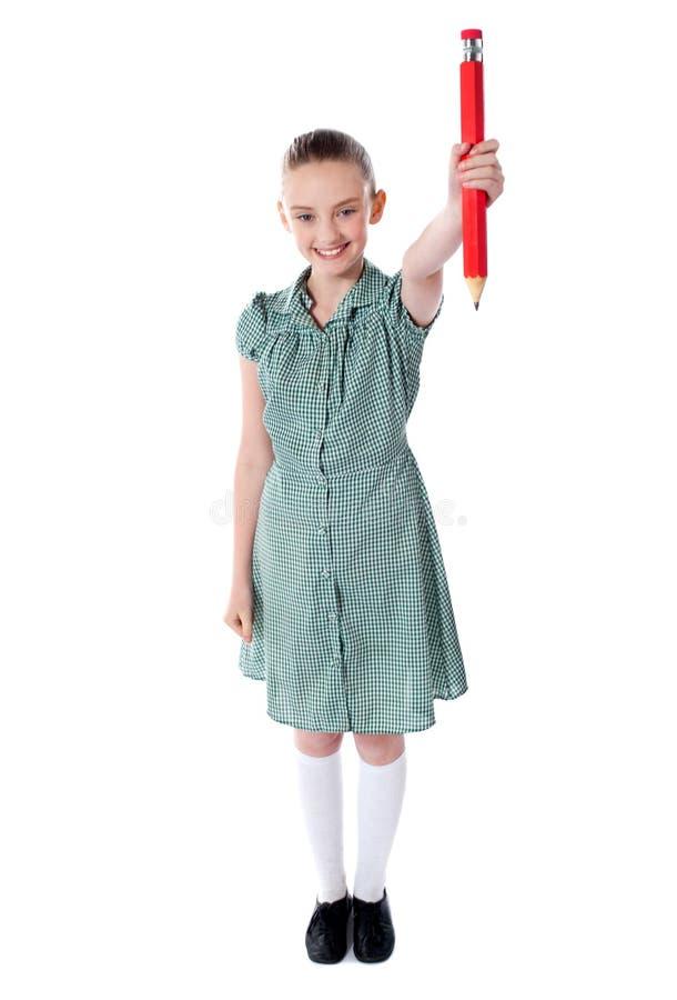 Aantrekkelijk meisje dat groot rood potlood toont royalty-vrije stock foto's