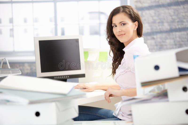 Aantrekkelijk meisje dat in het heldere bureau glimlachen werkt royalty-vrije stock afbeeldingen