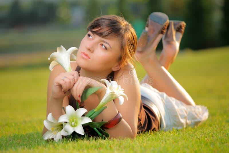 Aantrekkelijk meisje dat op het gras ligt stock fotografie