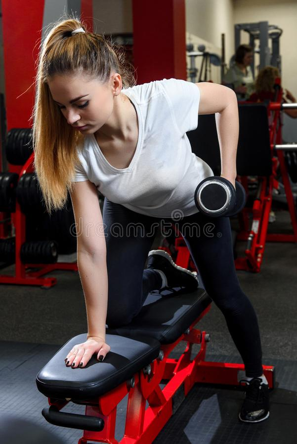 Aantrekkelijk meisje die actief met domoor in een gymnastiek uitwerken stock foto's