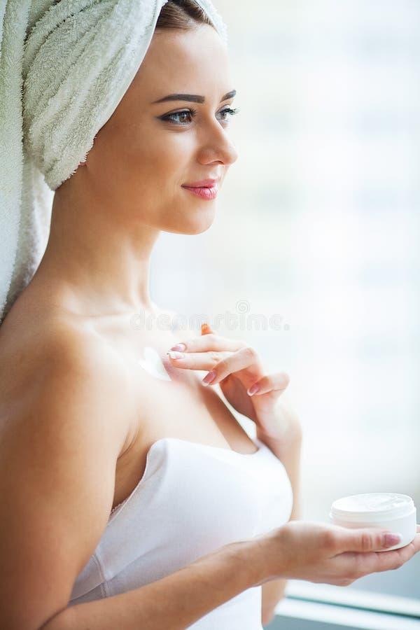 Aantrekkelijk meisje die anti-veroudert room op haar gezicht zetten royalty-vrije stock fotografie