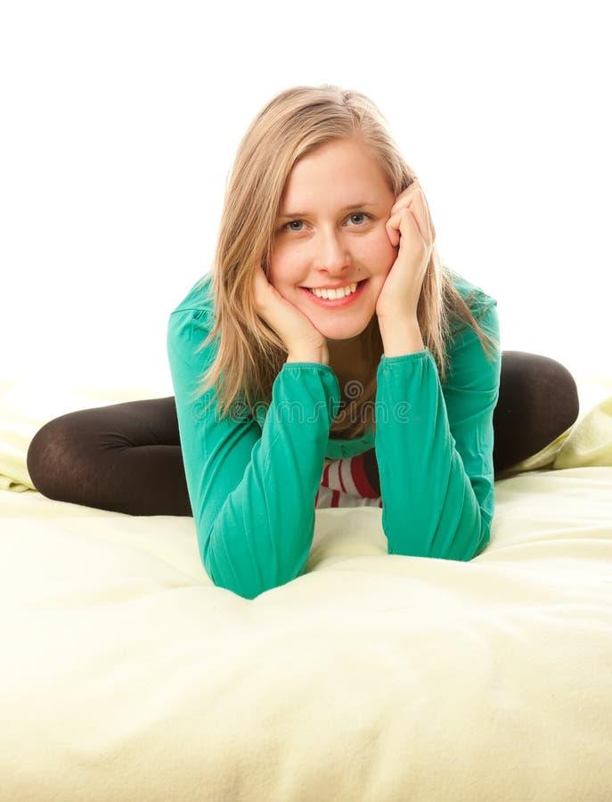 Aantrekkelijk meisje die in bed glimlachen stock afbeeldingen