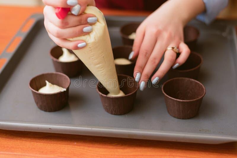 Aantrekkelijk meisje die cupcakes, de foto van het close-up zijaanzicht maken de vrouw leert te maken cupcakes stock foto