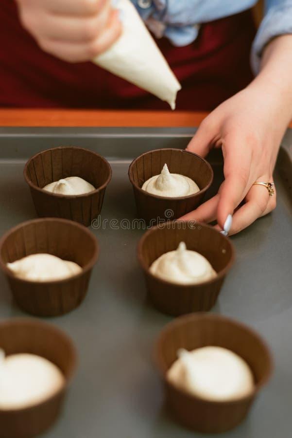 Aantrekkelijk meisje die cupcakes, de foto van het close-up zijaanzicht maken de vrouw leert te maken cupcakes royalty-vrije stock afbeeldingen