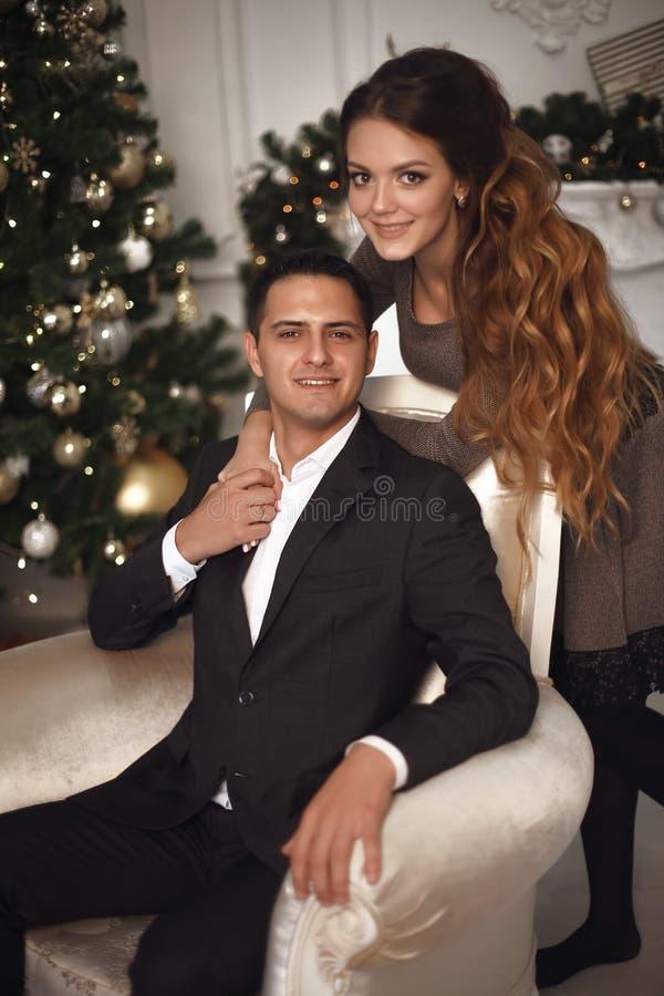 Aantrekkelijk meisje die de knappe mens op leunstoel koesteren Romantische coupl royalty-vrije stock afbeelding