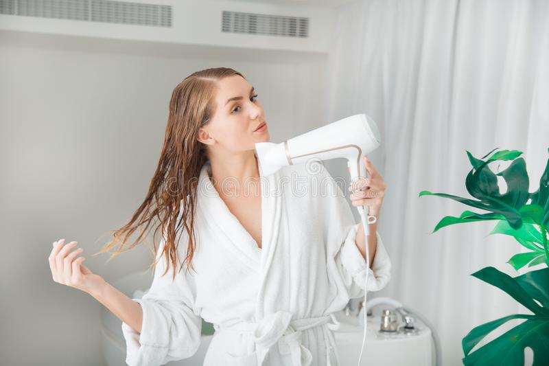 Aantrekkelijk meisje die haar nat haar drogen door hairdryer stock fotografie