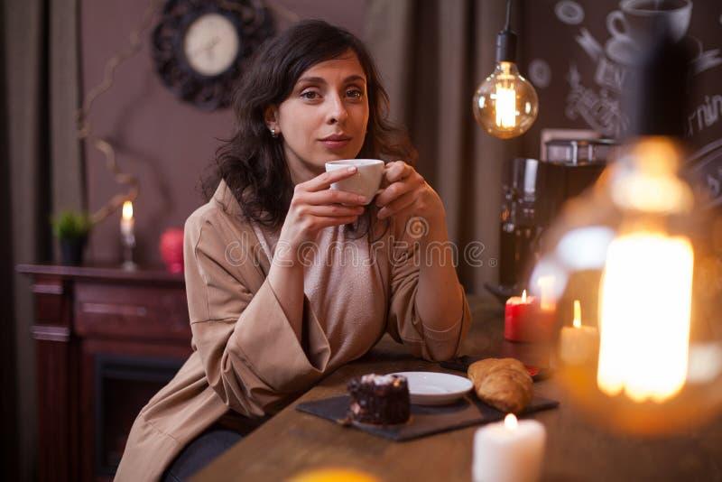 Aantrekkelijk meisje die heerlijke koffie drinken en de camera in een koffiebar bekijken stock afbeelding
