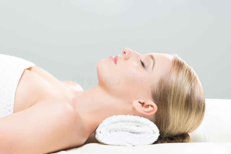 Aantrekkelijk meisje die op een mat in massagesalon leggen over de grijze achtergrond stock foto's