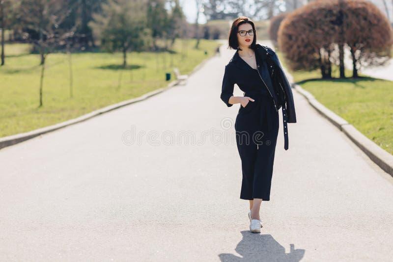 aantrekkelijk meisje die op parkweg lopen in zonnige dag stock fotografie
