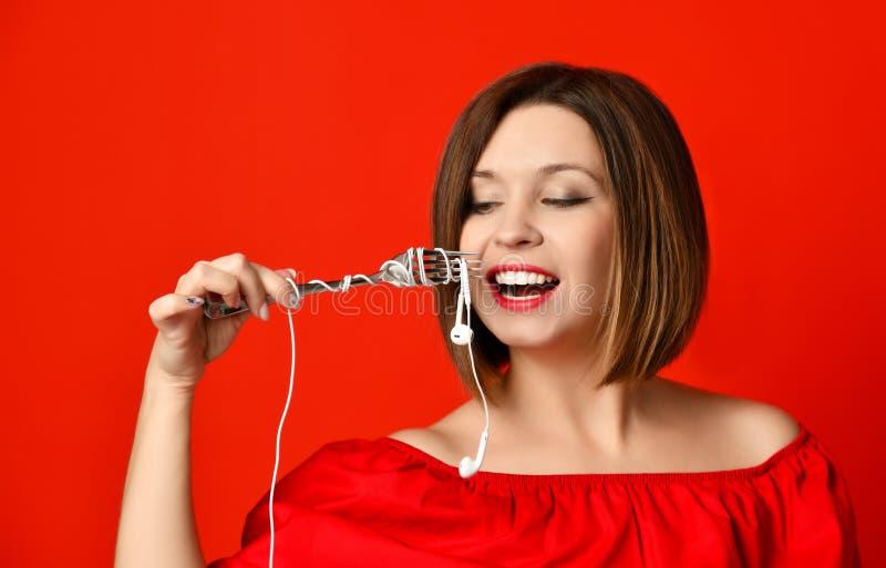 Aantrekkelijk meisje die in rode kleding een vork in handen houden op de hoofdtelefoonstop Trof te eten voorbereidingen royalty-vrije stock foto