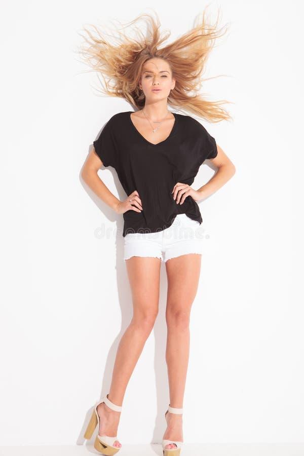 Aantrekkelijk meisje die terwijl de wind haar haar knoeit stellen stock foto's