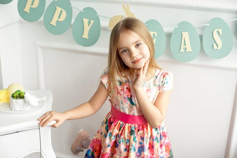Aantrekkelijk meisje in kleurrijke kleding die en tegen de achtergrond van een verfraaide lijst stellen glimlachen royalty-vrije stock afbeeldingen