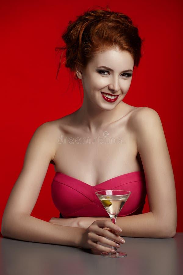 Aantrekkelijk meisje met cocktail, rode achtergrond royalty-vrije stock afbeelding